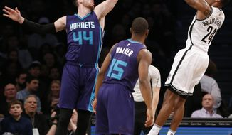 Charlotte Hornets' center Frank Kaminsky III (44) defends Brooklyn Nets forward Rondae Hollis-Jefferson (24) as Hornets guard Kemba Walker (15) watches in the first half of an NBA basketball game, Monday, Dec. 26, 2016, in New York. (AP Photo/Kathy Willens)
