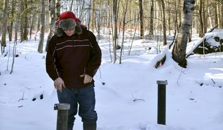 In this Friday, Dec. 16, 2016 photo, Richard Higgins, whose family's well water has been contaminated by a suspected carcinogen from a Dartmouth dump site, looks down at one of many test wells installed to monitor the groundwater in Hanover, N.H. Dartmouth College said it has spent around $8.4 million cleaning up contamination where scientists dumped carcasses of lab animals in the 1960s and 1970s. (AP Photo/Michael Casey)