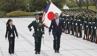 FILE - In this Dec. 7, 2016 file photo, U.S. Secretary of Defense Ash Carter, third from left, accompanied by Japanese Defense Minister Tomomi Inada, left, inspects an honor guard at the Defense Ministry Tokyo. Japan and the U.S. have agreed in principle on guidelines for limiting immunity from Japanese prosecution for civilian workers at American military bases, following a murder case this year on Okinawa involving a Marine-turned-contractor, officials said Monday, Dec. 26. (AP Photo/Eugene Hoshiko, File)