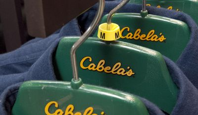 FILE- In this Feb. 16, 2011, garments hang in a Cabela's store in LaVista, Neb. Cabela's announcement in October 2016 that it will sell itself to rival outdoor gear seller Bass Pro for $4.5 billion was the year's No. 3 story as voted by Associated Press newspaper and broadcast members. (AP Photo/Nati Harnik, file)