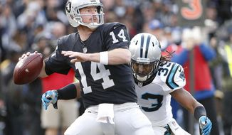 FILE - In this Nov. 27, 2016, file photo, Oakland Raiders quarterback Matt McGloin (14) drops back as Carolina Panthers free safety Tre Boston (33) applies pressure during the second half of an NFL football game in Oakland, Calif. After losing star quarterback Derek Carr to a broken leg, the Raiders now turn to McGloin with the AFC West title on the line in the season finale at Denver. (AP Photo/Tony Avelar, File)