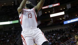 Houston Rockets guard James Harden (13) drives past Phoenix Suns guard Devin Booker (1) to the basket for a layup in the first half of an NBA basketball game on Monday, Dec. 26, 2016 in Houston. (AP Photo/Bob Levey)