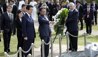 Sal Miwa, of the Japan-America Society of Hawaii, center, shows Japanese Prime Minister Shinzo Abe the Ehime Maru Memorial, Monday, Dec. 26, 2016, in Honolulu. The memorial is dedicated to the victims of a 2001 collision off the coast of Hawaii between the Ehime Maru, a fisheries training vessel, and a U.S. naval submarine. Several were killed, including four high school students, in the accidental collision. Shinzo Abe arrived in Hawaii on Monday to recognize the Japanese attacks on Pearl Harbor. (AP Photo/Marco Garcia)