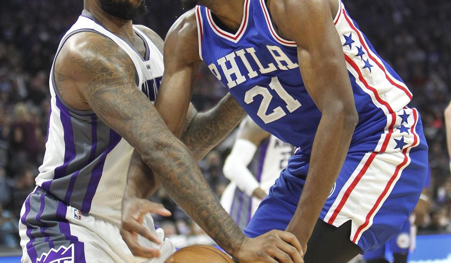 Philadelphia 76ers center Joel Embiid (21) battles for a loose ball with Sacramento Kings center DeMarcus Cousins (15) during the first half of an NBA basketball game in Sacramento, Calif., Monday, Dec. 26, 2016. (AP Photo/Steve Yeater)