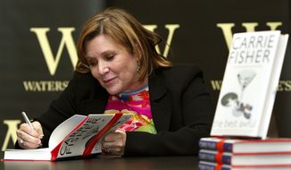 """In this Friday, Feb. 20, 2004 photo, author Carrie Fisher autographs her new book """"The Best Awful"""" at a promotional event in London. On Tuesday, Dec. 27, 2016, a publicist said Fisher has died at the age of 60. (AP Photo/John D. McHugh, File)"""