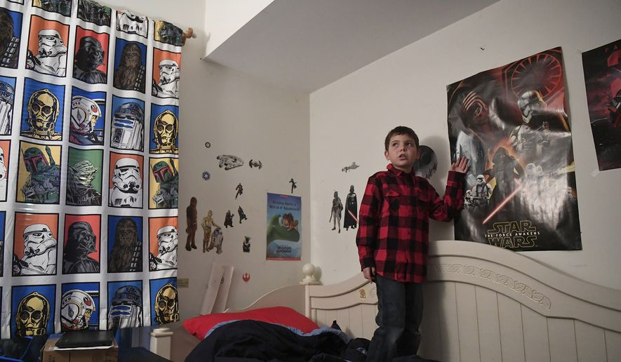 In this Dec. 13, 2016, photo, Joe Maldonado, 8 stands in his room in Secauscus, N.J. The family of Maldonado says he was kicked out of Cub Scouts because he is transgender, a move that could open a new front in the debate over discrimination in Scouting. (Danielle Parhizkaran/Northjersey.com via AP)