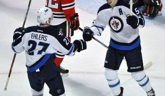 Winnipeg Jets' Mark Scheifele (55) celebrates with teammate Nikolaj Ehlers (27) after scoring a goal during the first period of an NHL hockey game against the Chicago Blackhawks Tuesday, Dec. 27, 2016, in Chicago. (AP Photo/Paul Beaty)