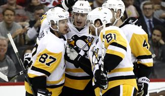 Pittsburgh Penguins celebrate a goal by center Evgeni Malkin, second from left, of Russia, during the first period of an NHL hockey game against the New Jersey Devils, Tuesday, Dec. 27, 2016, in Newark, N.J. (AP Photo/Julio Cortez)
