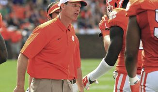 FILE - In this April 11, 2015, file photo, Clemson defensive coordinator Brent Venables, left, gets on a player during Clemson's NCAA college football spring game at Memorial Stadium in Clemson, S.C. Clemson fans no doubt are accustomed to the sight: defensive coordinator Brent Venables charging onto the field in an emotional outburst, being pulled back to the sideline by the assistant strength coach in charge keeping the intense coach out of trouble. (Mark Crammer/Anderson Independent-Mail via AP, File)