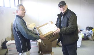 In this photo provided by Joseph Roginski, taken May 13, 2011, Joseph Roginski, right, holds a package in a storeroom of the Misawa City Hall in Japan, where donations of clothing and supplies were being kept for earthquake relief efforts. He says that while the cost of living is higher in Japan, access to health care is not. (Joseph Roginski via AP)