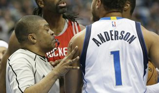 Houston Rockets center Nene Hilario, center, and Dallas Mavericks guard Justin Anderson (1) are separated by referee Tony Brothers, left, as they argue during the first half of an NBA basketball game in Dallas, Tuesday, Dec. 27, 2016. (AP Photo/LM Otero)