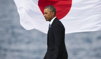 U.S. President Barack Obama walks past a Japanese flag at Joint Base Pearl Harbor-Hickam, Tuesday, Dec. 27, 2016, in Honolulu. Abe and Obama made a historic pilgrimage Tuesday to the site where the devastating surprise attack sent America marching into World War II. (AP Photo/Marco Garcia)