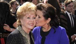 "In this Sept. 10, 2011, file photo, Debbie Reynolds, left, and Carrie Fisher arrive at the Primetime Creative Arts Emmy Awards in Los Angeles. Reynolds, star of the 1952 classic ""Singin' in the Rain"" died Wednesday, Dec. 28, 2016, according to her son Todd Fisher. She was 84. (AP Photo/Chris Pizzello, File)"
