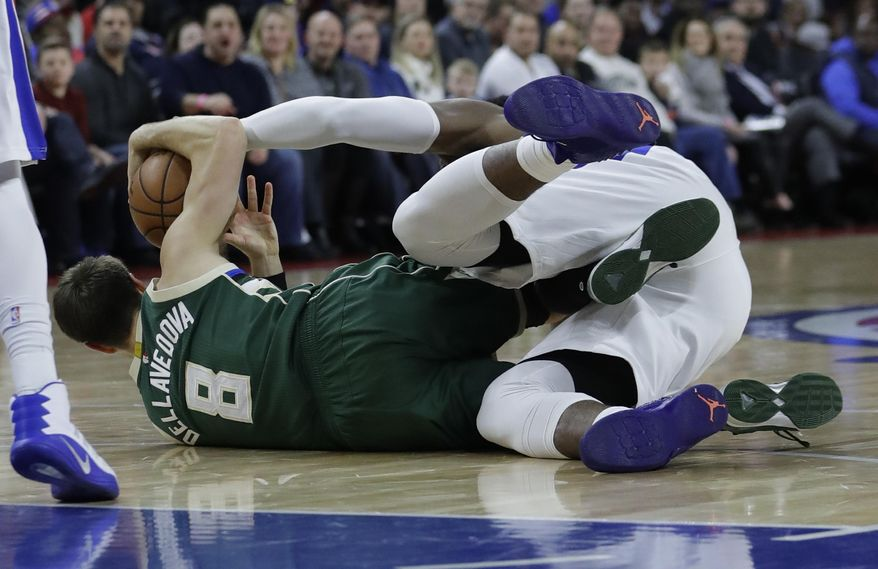Milwaukee Bucks guard Matthew Dellavedova (8) and Detroit Pistons center Andre Drummond battle for the loose ball during the first half of an NBA basketball game, Wednesday, Dec. 28, 2016, in Auburn Hills, Mich. (AP Photo/Carlos Osorio)