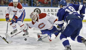 Montreal Canadiens goalie Carey Price (31) reaches back to make the save on a shot by Tampa Bay Lightning left wing Ondrej Palat (18), of the Czech Republic, during the second period of an NHL hockey game Wednesday, Dec. 28, 2016, in Tampa, Fla. Defending for Montreal is defenseman Nathan Beaulieu (28). (AP Photo/Chris O'Meara)