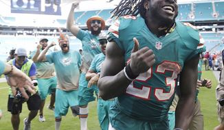 FILE - In this Oct. 23, 2016, file photo, Miami Dolphins running back Jay Ajayi is congratulated as he leaves the field at the end of an NFL football game against the Buffalo Bills in Miami Gardens, Fla. Ajayi has had three 200-yard games this season, and is eager to show what he can do in the playoffs. (AP Photo/Lynne Sladky)