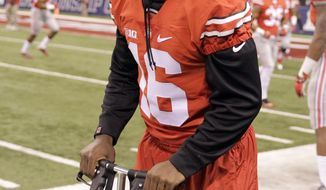 FILE - In a Saturday, Dec. 6, 2014 file photo, injured Ohio State quarterback J.T. Barrett is seen on the sidelines before the start of the Big Ten Conference championship NCAA college football game between Ohio State and Wisconsin, in Indianapolis. In 2016, a healthy, confident Barrett led the Buckeyes to an 11-1 record and a spot in the College Football Playoff against Clemson on New Year's Eve. Instead of being relegated to the fringe, he's now is at the center of intense bowl game prep with a chance to play for another national championship. (AP Photo/Darron Cummings, File)