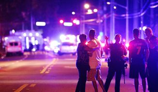 In this June 12, 2016, file photo, Orlando Police officers direct family members away from a fatal shooting at Pulse nightclub in Orlando, Fla. (AP Photo/Phelan M. Ebenhack, File)