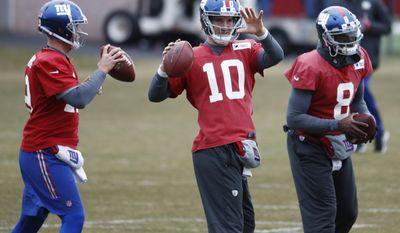 New York Giants quarterbacks, from left, Keith Wenning, Eli Manning and Josh Johnson work out during NFL football practice, Wednesday, Dec. 28, 2016, in East Rutherford, N.J. (AP Photo/Julio Cortez)