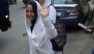 In this photo provided by Basel Hijawi, taken in 2015, American citizen Aya Hijazi waves as she leaves a court in Cairo after hearing. Family and friends of an American jailed in Egypt for nearly three years are hoping her time in custody may end soon. Hijazi, 29, grew up in Falls Church, Va. and is a dual citizen of the U.S. and Egypt. After receiving her degree in conflict resolution from George Mason University in 2009, she returned to her native country, and with her Egyptian husband, started a foundation to help homeless children. (Basel Hijawi via AP)