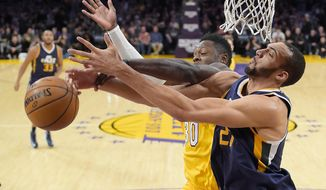 Los Angeles Lakers forward Julius Randle, left, and Utah Jazz center Rudy Gobert vie for a rebound during the first half of an NBA basketball game, Tuesday, Dec. 27, 2016, in Los Angeles. (AP Photo/Mark J. Terrill)