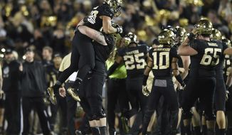 Wake Forest offensive lineman Justin Herron lifts running back Matt Colburn after Wake Forest defeated Temple 34-26 in the Military Bowl NCAA college football game, Tuesday, Dec. 27, 2016 in Annapolis, Md. (AP Photo/Gail Burton)