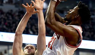 Chicago Bulls forward Jimmy Butler (21) shoots against Brooklyn Nets guard Bojan Bogdanovic, left, during the first half of an NBA basketball game Wednesday, Dec. 28, 2016, in Chicago. (AP Photo/Matt Marton)