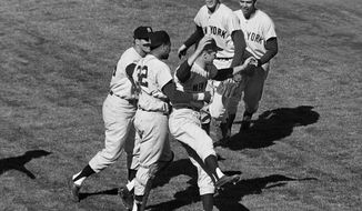 FILE - In this Oct. 16, 1962, file photo, New York Yankees players celebrate at Candlestick Park, after defeating the San Francisco Giants 1-0 in Game 7 of the baseball World Series. In group at center, first baseman Bill Skowron, left, and catcher Elston Howard (32) rush winning pitcher Ralph Terry. In the background are shortstop Tony Kubek, left, and second baseman Bobby Richardson. Richardson was was with the Yankees at the tail end of what is generally viewed as the greatest dynasty of them all--a 44-year stretch that, beginning in 1921, produced 20 World Series titles, 29 American League pennants, 43 winning seasons and only two finishes lower than third in the AL standings. Over his first eight full seasons with the Yankees, he went to the World Series seven times. (AP Photo/File)