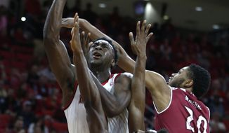 North Carolina State's Abdul-Malik Abu, left, shoots while Rider's Kahlil Thomas, bottom, and Tyere Marshall (20) defend during the first half of an NCAA college basketball game in Raleigh, N.C., Wednesday, Dec. 28, 2016. (Ethan Hyman/The News & Observer via AP)