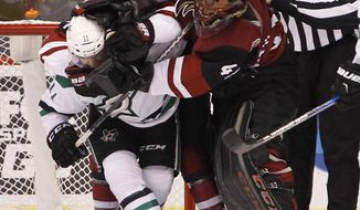 Arizona Coyotes goalie Mike Smith (41) and defenseman Anthony DeAngelo (77) tangle with Dallas Stars' Curtis McKenzie (11) after a play in front of the net during the second period of an NHL hockey game, Tuesday, Dec. 27, 2016, in Glendale, Ariz. (AP Photo/Ralph Freso)
