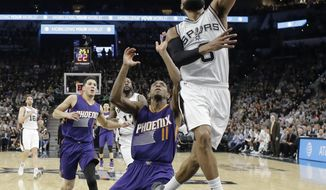 San Antonio Spurs guard Patty Mills (8) scores past Phoenix Suns guard Brandon Knight (11) during the first half of an NBA basketball game, Wednesday, Dec. 28, 2016, in San Antonio. (AP Photo/Eric Gay)