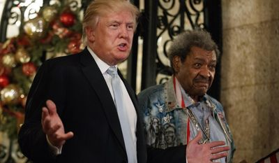 President-elect Donald Trump, left, stands with boxing promoter Don King as he speaks to reporters at Mar-a-Lago, Wednesday, Dec. 28, 2016, in Palm Beach, Fla. (AP Photo/Evan Vucci)