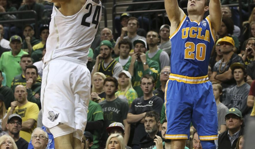 UCLA's Bryce Alford, right, shoots a three point shot over Oregon's Dillon Brooks, left, during the second half of an NCAA college basketball game Wednesday, Dec. 28, 2016, in Eugene, Ore. (AP Photo/Chris Pietsch)