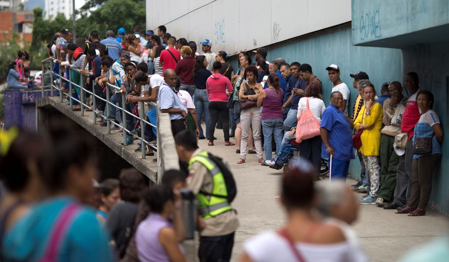 People wait outside a supermarket to buy government subsided food in Caracas, Venezuela. As domestic production dries up in Venezuela, the state has given itself the role of importing nearly all the country's food. (Associated Press)