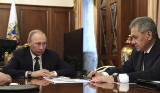 Russian President Vladimir Putin, left, listens to Defence Minister Sergei Shoigu in Moscow, Russia on Thursday, Dec. 29, 2016. Putin is ordering to scale down the Russian military presence in Syria. Putin made the statement Thursday while declaring that a cease-fire in Syria brokered by Russia and Turkey will start at midnight. (Mikhail Klimentyev/Sputnik, Kremlin Pool Photo via AP)