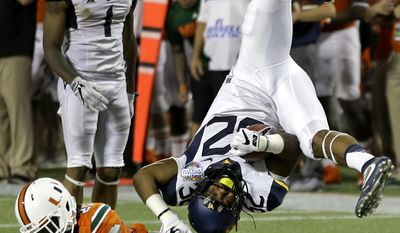 West Virginia running back Martell Pettaway, right, is upended by Miami defensive back Adrian Colbert (25) during the second half of the Russell Athletic Bowl NCAA college football game, Wednesday, Dec. 28, 2016, in Orlando, Fla. Miami won 31-14. (AP Photo/John Raoux)