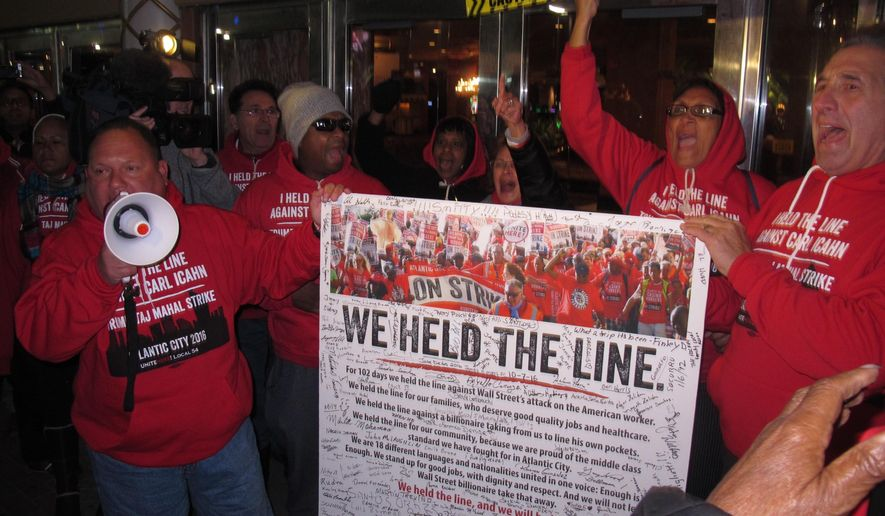 In this Oct. 10, 2016, photo, striking union members protest outside the Trump Taj Mahal casino in Atlantic City, N.J., moments before it shut down. Whether owner Carl Icahn tries to reopen the building built in 1990 by incoming President Donald Trump is one of the big questions facing Atlantic City in 2017. (AP Photo/Wayne Parry)