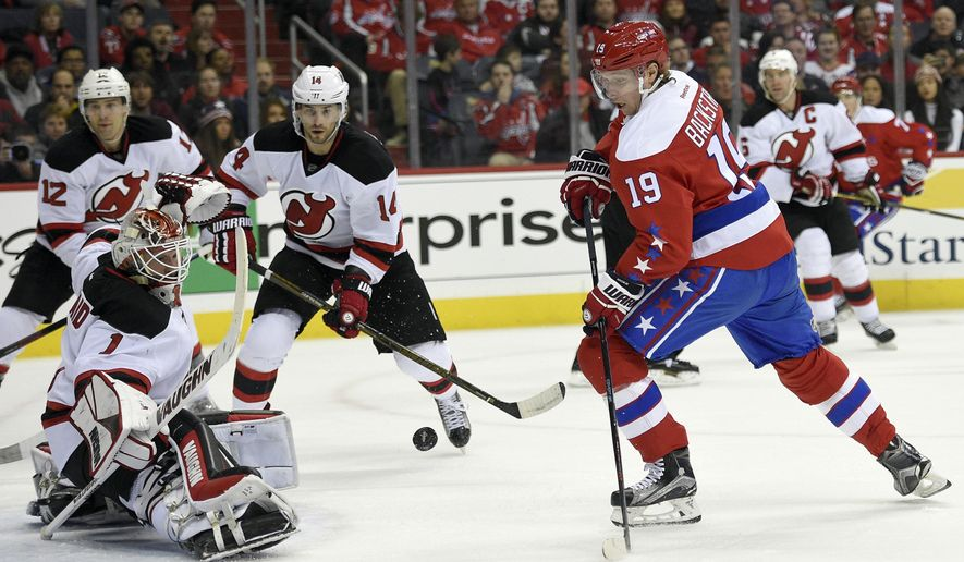 New Jersey Devils goalie Keith Kinkaid (1) watches the puck as Washington Capitals center Nicklas Backstrom (19), of Sweden, looks on during the first period of an NHL hockey game, Thursday, Dec. 29, 2016, in Washington. Devils defenseman Ben Lovejoy (12) and center Adam Henrique (14) watch the play. (AP Photo/Nick Wass)