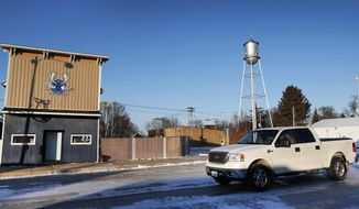 A pickup truck passes the Blue Moose Saloon which opened in September in Renwick, Iowa, on Tuesday, Dec. 13, 2016. Once-bustling Renwick has lost many businesses as its population declined, but when the town's sole bar closed this year, a group of friends pooled their money to repair and reopen the place as the Blue Moose Saloon. They said without a meeting place, Renwick wouldn't be much of a town. (AP Photo/Charlie Neibergall)