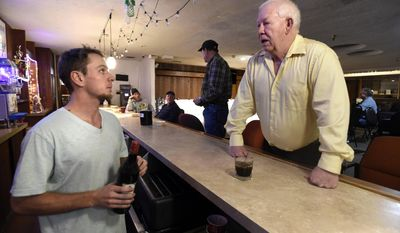 In this Tuesday, Dec. 20, 2016 photo, bartender Zack Terbest takes a drink order from Jim Barnett during the dinner and dance night at the Elks Lodge in Boulder, Colo. (Jeremy Papasso /Daily Camera via AP)