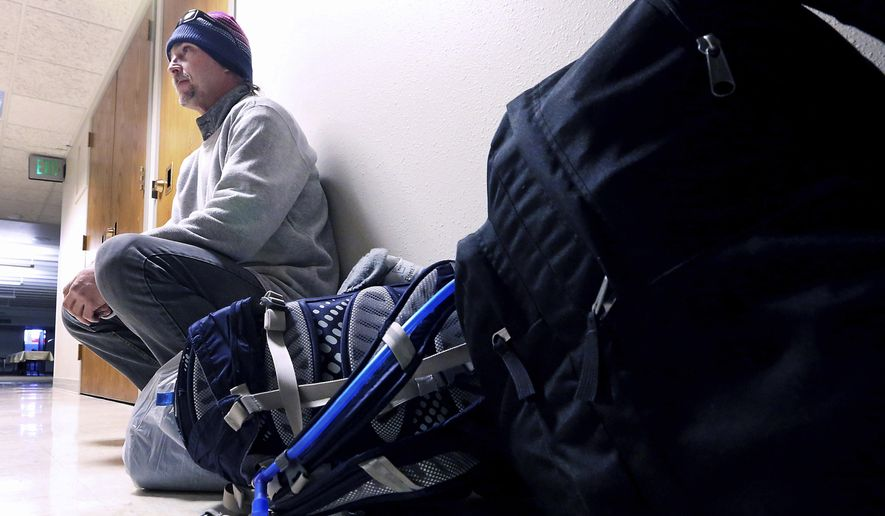 In this Monday, Dec. 19, 2016 photo, Robert Morrison, who has been homeless in Madison, Wis., for four years, waits with some of his belongings at Bethel Lutheran Church's day shelter downtown. Advocates are seeking to provide secure storage and other assistance aimed at helping the homeless be more mobile. (John Hart/Wisconsin State Journal via AP)