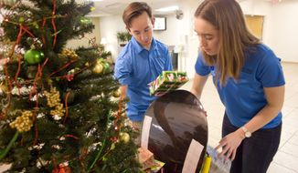 ADVANCE FOR SATURDAY, DEC. 31, 2016 - In this Wednesday, Dec. 14, 2016 photo, Junior Volunteers Felicity Pollard and Zac Dockins check on the Christmas For Kids Sharing Tree at Gritman Medical Center in Moscow, Idaho. The Junior Volunteers organized the sharing tree. (Geoff Crimmins /The Moscow-Pullman Daily News via AP)