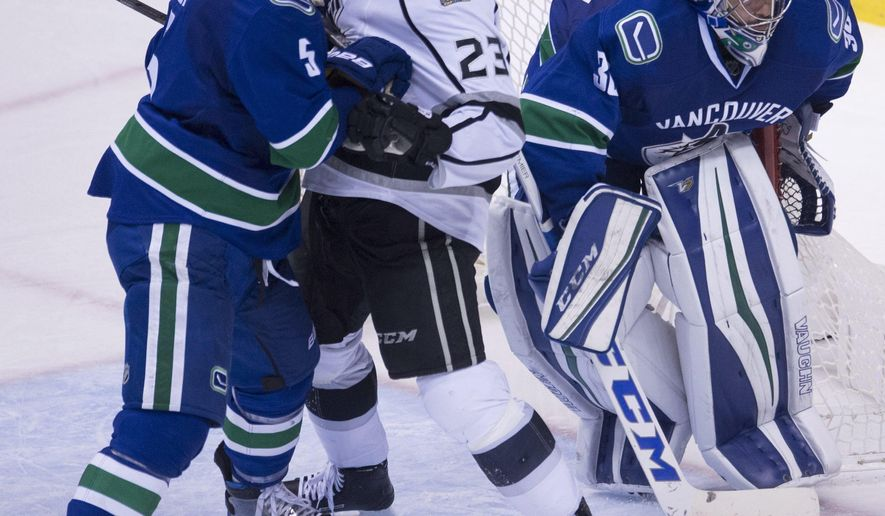 Vancouver Canucks defenseman Luca Sbisa (5) tries to clear Los Angeles Kings right wing Dustin Brown (23) from in front of Canucks goalie Ryan Miller (30) during the third period of an NHL hockey game Wednesday, Dec. 28, 2016, in Vancouver, British Columbia. (Jonathan Hayward/The Canadian Press via AP)