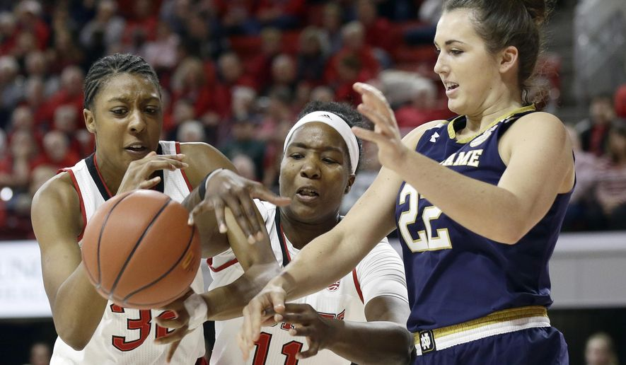 Notre Dame's Erin Boley (22) reaches for the ball with North Carolina State's Akela Maize, left, and Jennifer Mathurin (11) during the first half of an NCAA college basketball game in Raleigh, N.C., Thursday, Dec. 29, 2016. (AP Photo/Gerry Broome)