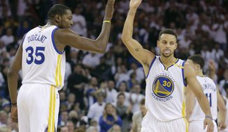 Golden State Warriors forward Kevin Durant (35) celebrates his scoring with guard Stephen Curry (30) during the first half of an NBA basketball game against the Toronto Raptors in Oakland, Calif., Wednesday, Dec. 28, 2016. (AP Photo/Jeff Chiu)
