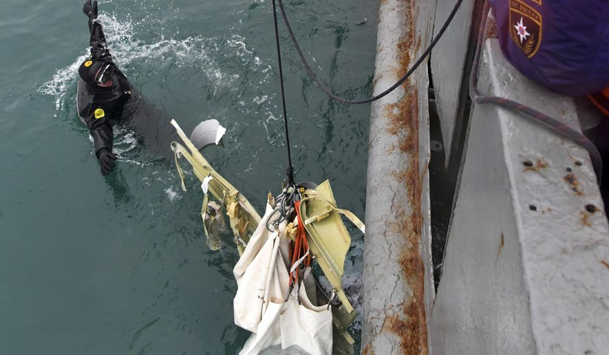 In this photo taken on Wednesday, Dec. 28, 2016, photo provided by the Russian Emergency Ministry Press Service, ministry employees lift a fragment of a plane in the Black Sea, outside Sochi, Russia. Russia's Defense Ministry says search teams have recovered another flight recorder from a military plane that crashed in the Black Sea, killing all 92 aboard. (Vladimir Velengurin/Emergency Situations Ministry Photo via AP)