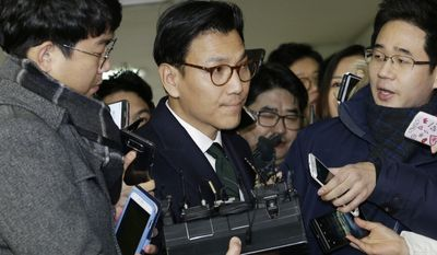 Kim Jae-youl, chief of the sports marketing unit of Samsung Group, center, arrives at the office of the independent counsel in Seoul, South Korea, Thursday, Dec. 29, 2016. South Korean investigators on Thursday summoned Kim as they look further into allegations that the business giant sponsored the president's jailed friend, Choi Soon-sil, to receive government favors. (AP Photo/Ahn Young-joon)