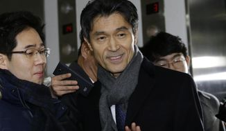 South Korea's ambassador to France Mo Chul-min, front right, arrives at the office of the independent counsel in Seoul, South Korea, Thursday, Dec. 29, 2016. South Korean investigators on Thursday summoned Mo as they widened their inquiry into a corruption scandal involving impeached President Park Geun-hye to include allegations that her administration blacklisted thousands of artists for their political beliefs. (AP Photo/Ahn Young-joon)