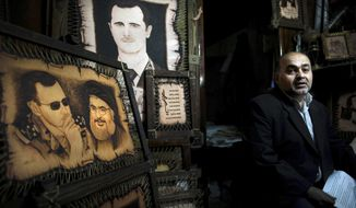 FILE -- In this Feb. 24, 2016 file photo, a Syrian shopkeeper waits for customers next to paintings of of President Bashar Assad, and Hezbollah leader Sheikh Hassan Nasrallah, center, at the Souk Tawil market in Damascus, Syria. Turkey said Thursday, Dec. 29, 2016, that Lebanon's militant Hezbollah group, which has sent thousands of fighters to support President Bashar Assad, should withdraw from Syria. In an interview with Turkey's A Haber news channel, Foreign Minister Mevlut Cavusoglu also said Turkey and Russia are close to reaching an agreement on a nationwide Syrian cease-fire that would come into effect by the end of the year. (AP Photo/Hassan Ammar, File)