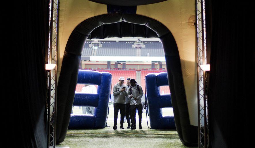 Washington players walk off the field during media day for Saturday's Peach Bowl NCAA college football game against Alabama in Atlanta, Thursday, Dec. 29, 2016. (AP Photo/David Goldman)